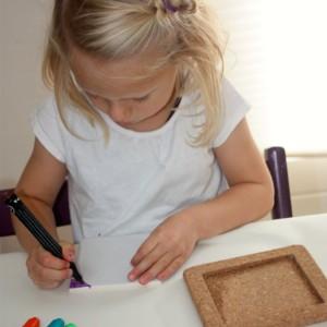 børn maler bordskåner af kork og flise med porcelænstuscher